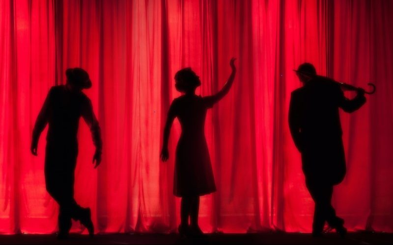 Performers in silhouette on stage