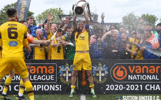 Sutton FC celebrate- holding cup and celebrating with fans in the background