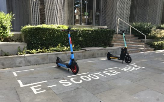 A picture of e-scooters parked in their designated bay which is on the pavement and marked with a white line. The photo was taken in Hammersmith
