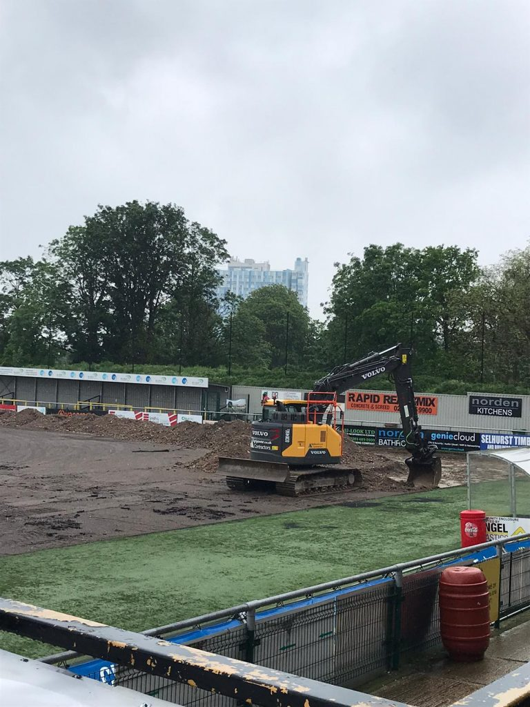 Image of digger removing the astro turf from the pitch.