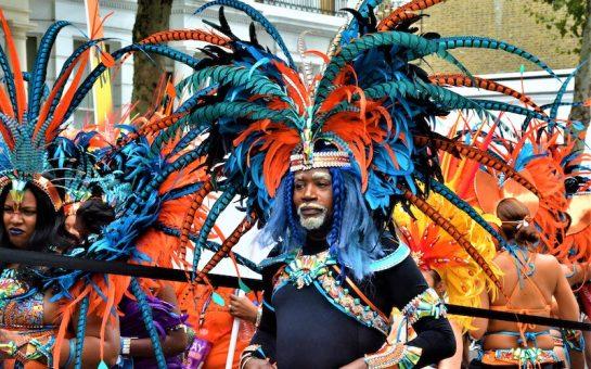 carnival procession. person in blue and orange headdress