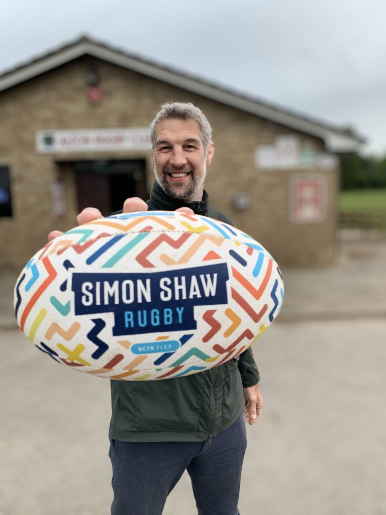 Ex-England international Simon Shaw holding a rugby ball toward the camera with Simon Shaw Rugby written on it and many colourful lines