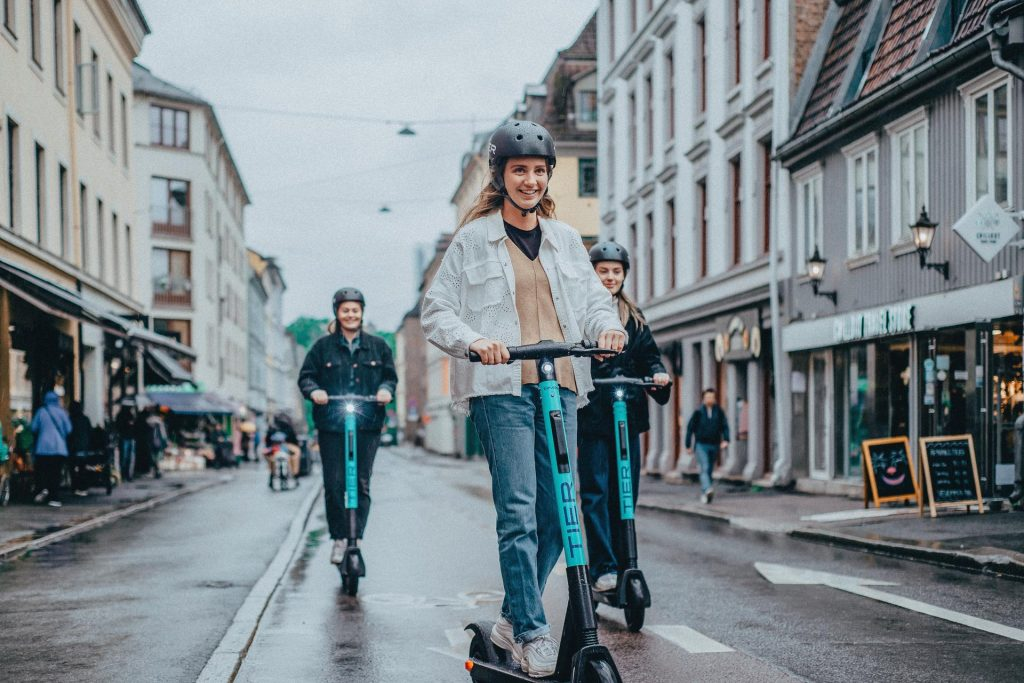 Smiling young people try out TIER e-scooters wearing helmets and scooting in a cycle lane in this promotional picture from Tier