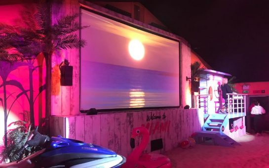 Miami Nights screen room with pink lighting, plam trees, a speed boat proper and an inflatable flamingo around the sides of the cinema screen. A sunset is on the screen.