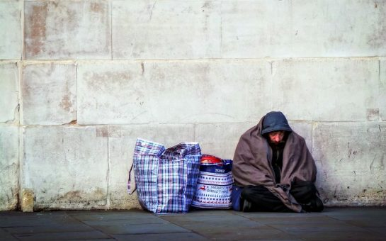 homeless man sitting up against a wall