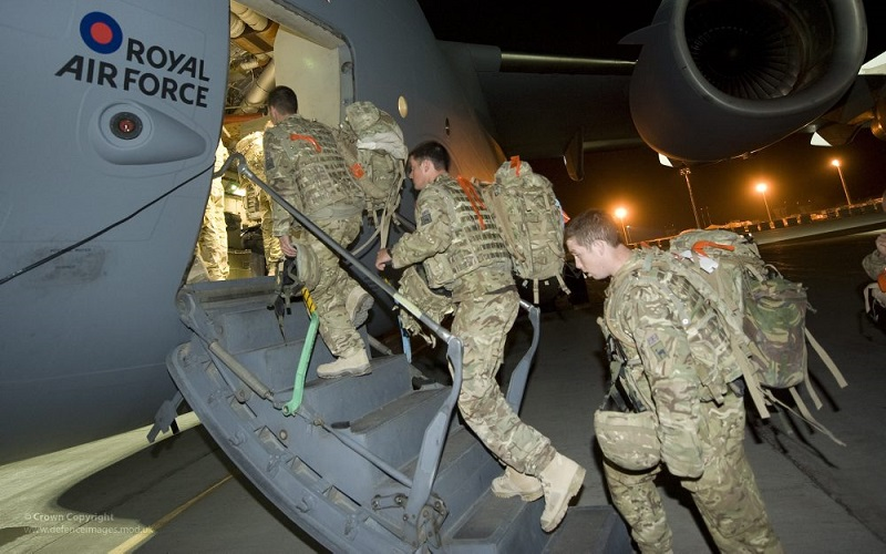 British army troops walking up a ramp into a cargo plane to return to the UK from Afghanistan