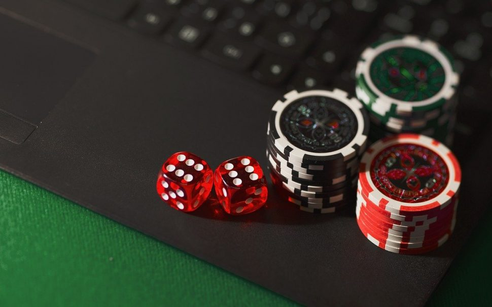 dice and poker chips on a laptop