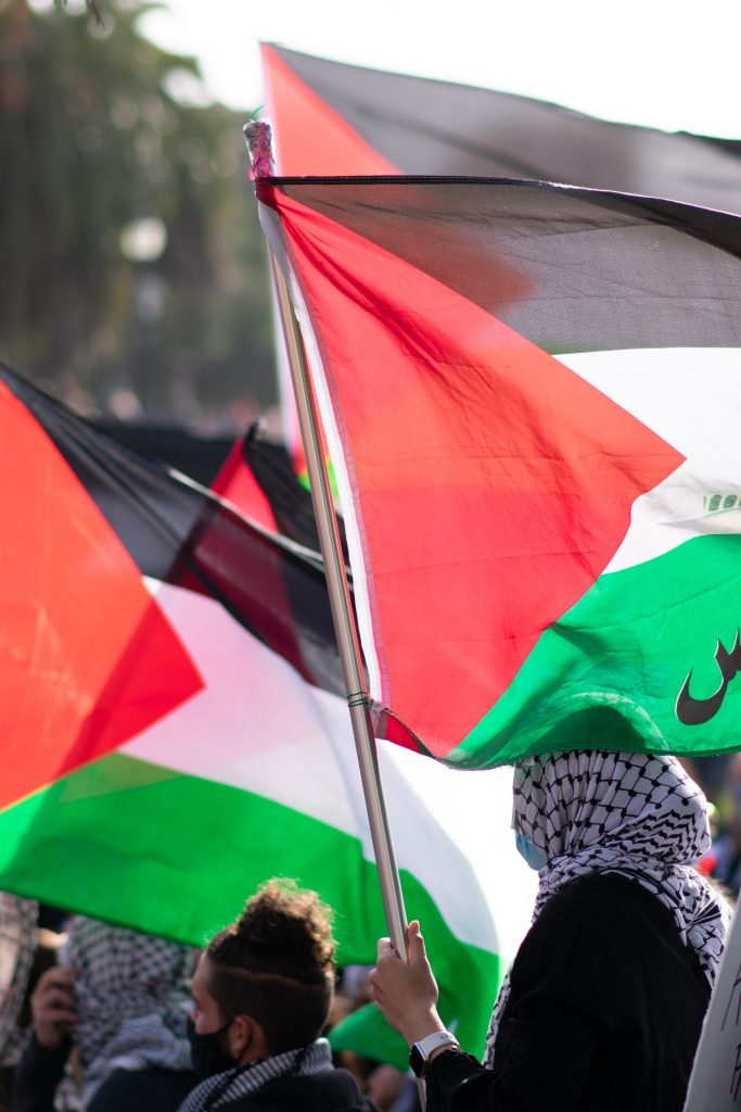Protesters for the Palestinian cause waving the flag, many of whom wear traditional 'khafiya' headscarves. Photo by Patrick Perkins on Unsplash