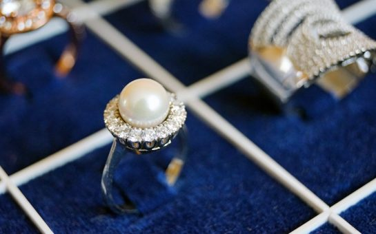 An image of a pearl ring surrounded by other jewellery sparkling in the background