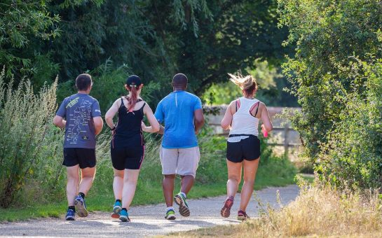 Four people running through the park
