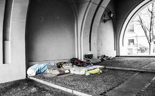 Sleeping bags and belongings under an archway from people sleeping rough