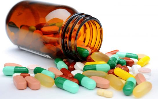 Multicoloured pills spilling out of a bottle onto a white table
