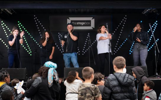People standing on stage outside, beatboxing