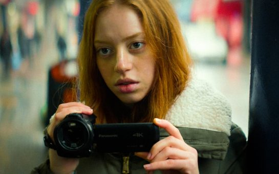 Lily Newmark as Leah, holding a video camera in scene from A Brixton Tale