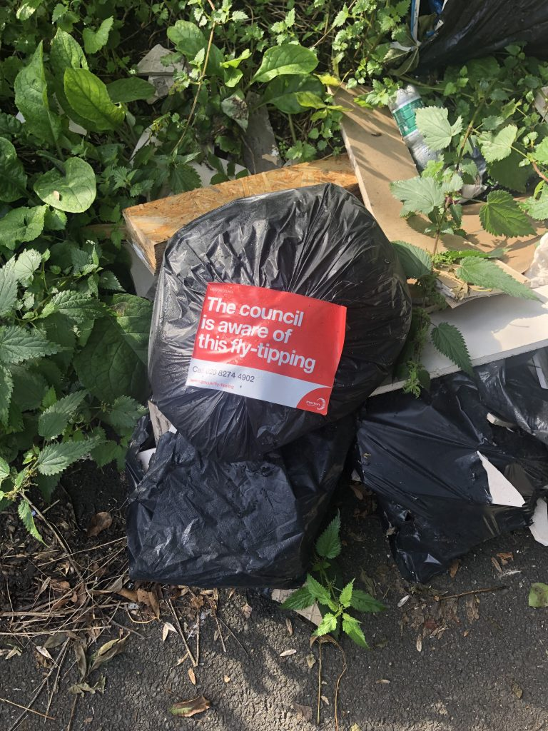 """Bag of Rubbish with sign by the council saying they are """"aware of this fly-tipping"""""""