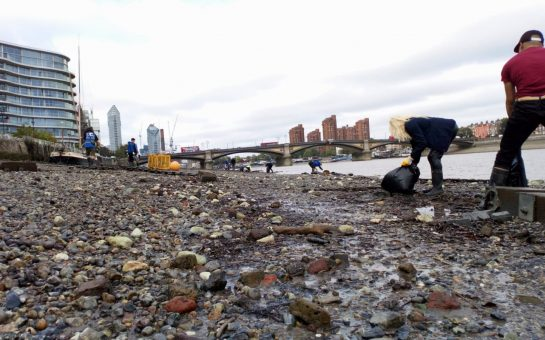 A polluted beach with the London skyline in the background