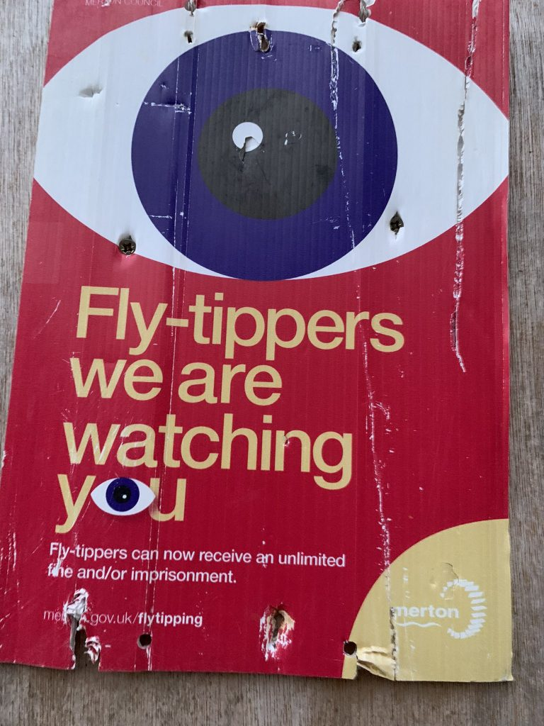 """Poster with large eye on a red background with the warning """"Fly-tippers we are watching you"""""""