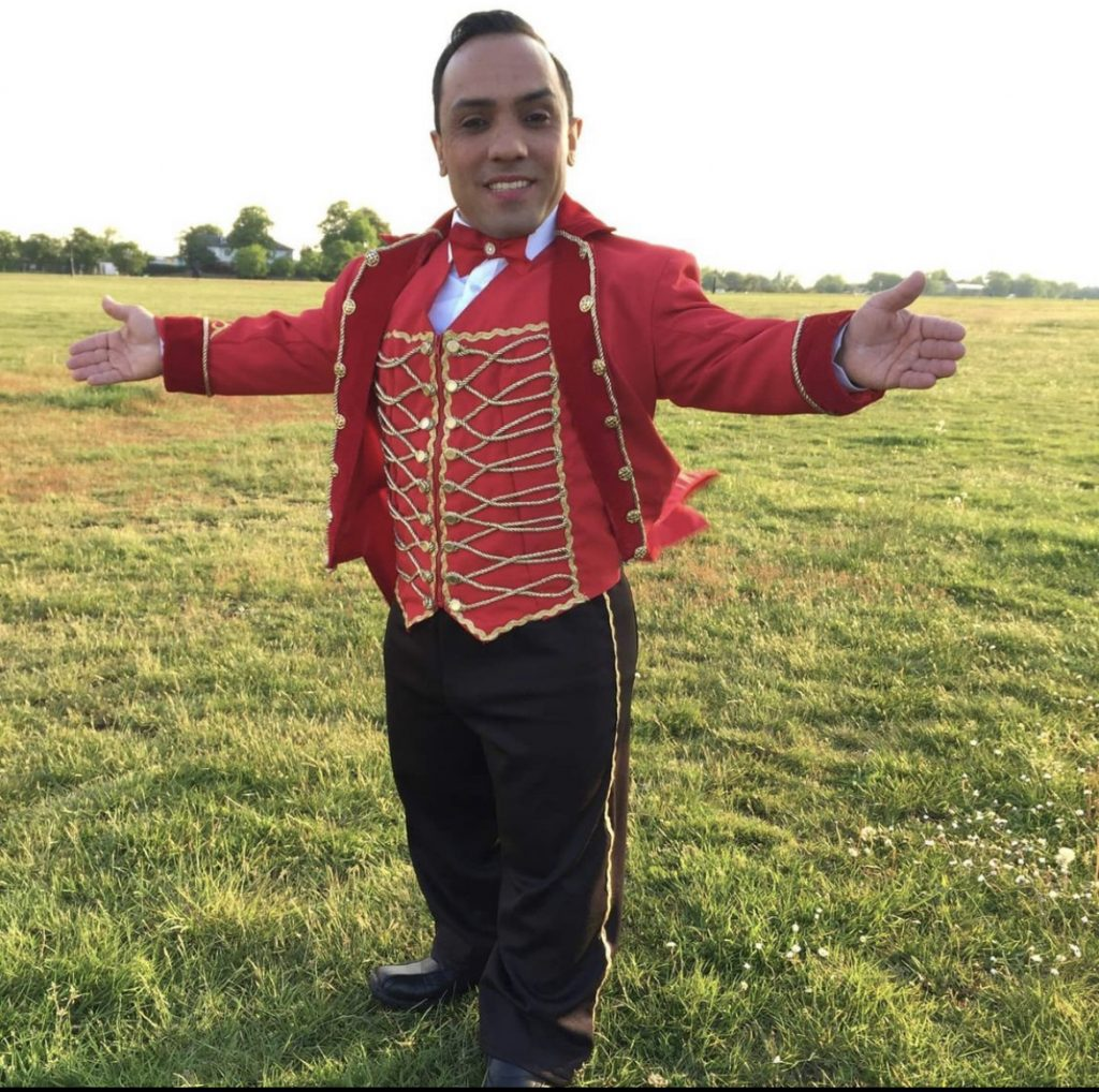 A photo of Paulo Dos Santos in a red ring master's jacket with gold detailing and buttons. His trousers are black with gold outer-lining. He is also wearing a red bow-tie. He is standing on a green field.