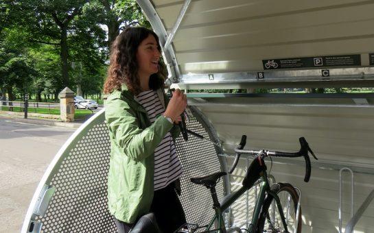 Woman locking her bike in storage space