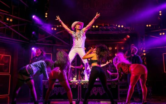 Kevin clifton is stnading with his arms up on a raised platform with the female ensemble facing him and touching the platform. He is wearing a white baggy vest with feather detailing and white jeans with a cowboy hat.