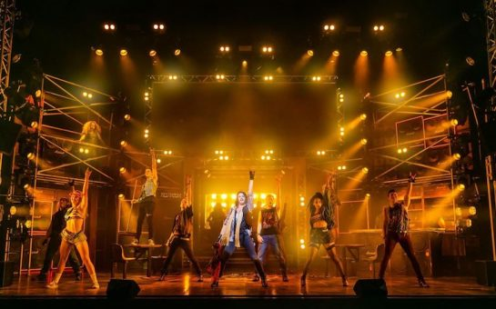 The cast are onstage spread out in a power stance with their left arm in the air. Lonny (Joe Gash) is in the middle.