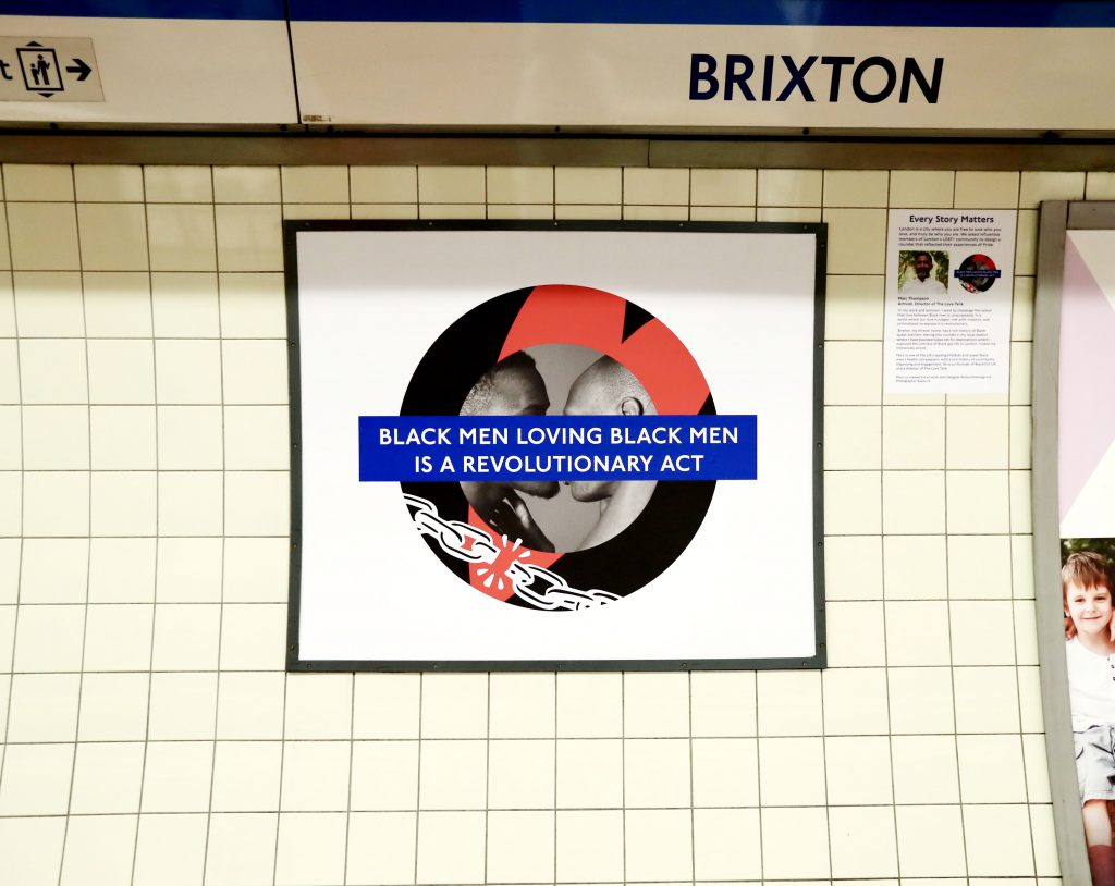 """Marc Thompson's Pride roundel in Brixton, featuring two black men kissing, a heart, broken chains and the words """"Black men loving black men is a revolutionary act."""""""