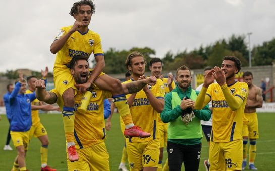 The Wimbledon players celebrating with the fans after their victory over Morecambe FC