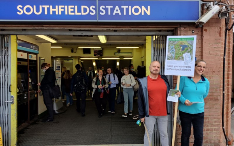 Wimbledon residents holding up a placard outside Southfields tube station.