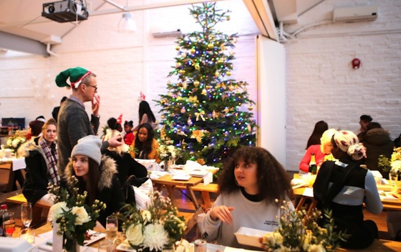 Young people sit at festively decorated tables with a Christmas tree in the background.