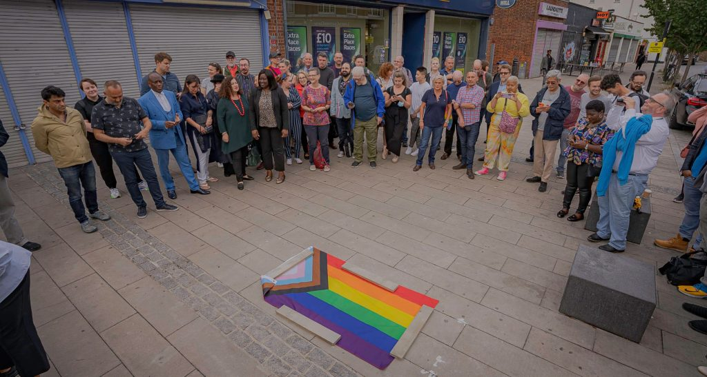 A crowd gathered around a progress pride flag covering the plaque at the unveiling ceremony