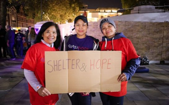 Three people hold sign saying Shelter & Hope