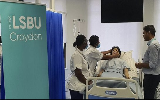 A photo of student nurses training on a dummy in a replica hospital ward in London South Bank University's new Croydon campus