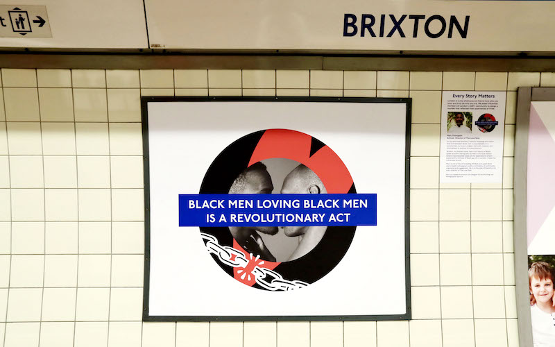"""The Brixton Pride roundel featuring two black men kissing with the words """"Black men loving black men is a revolutionary act."""""""
