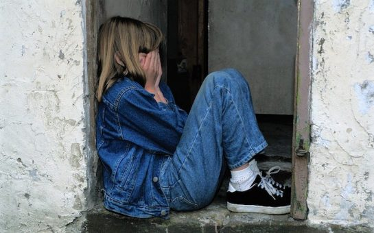 A child sitting on an outdoor step, face covered with her hands in fear