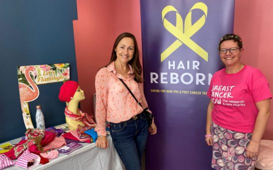 Anna Godsiff and Lina Milazzo smilimg in front a Hair Reborn stand with headwraps