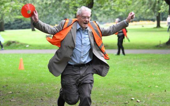 An elderly man in a high-vis vest finishes parkrun